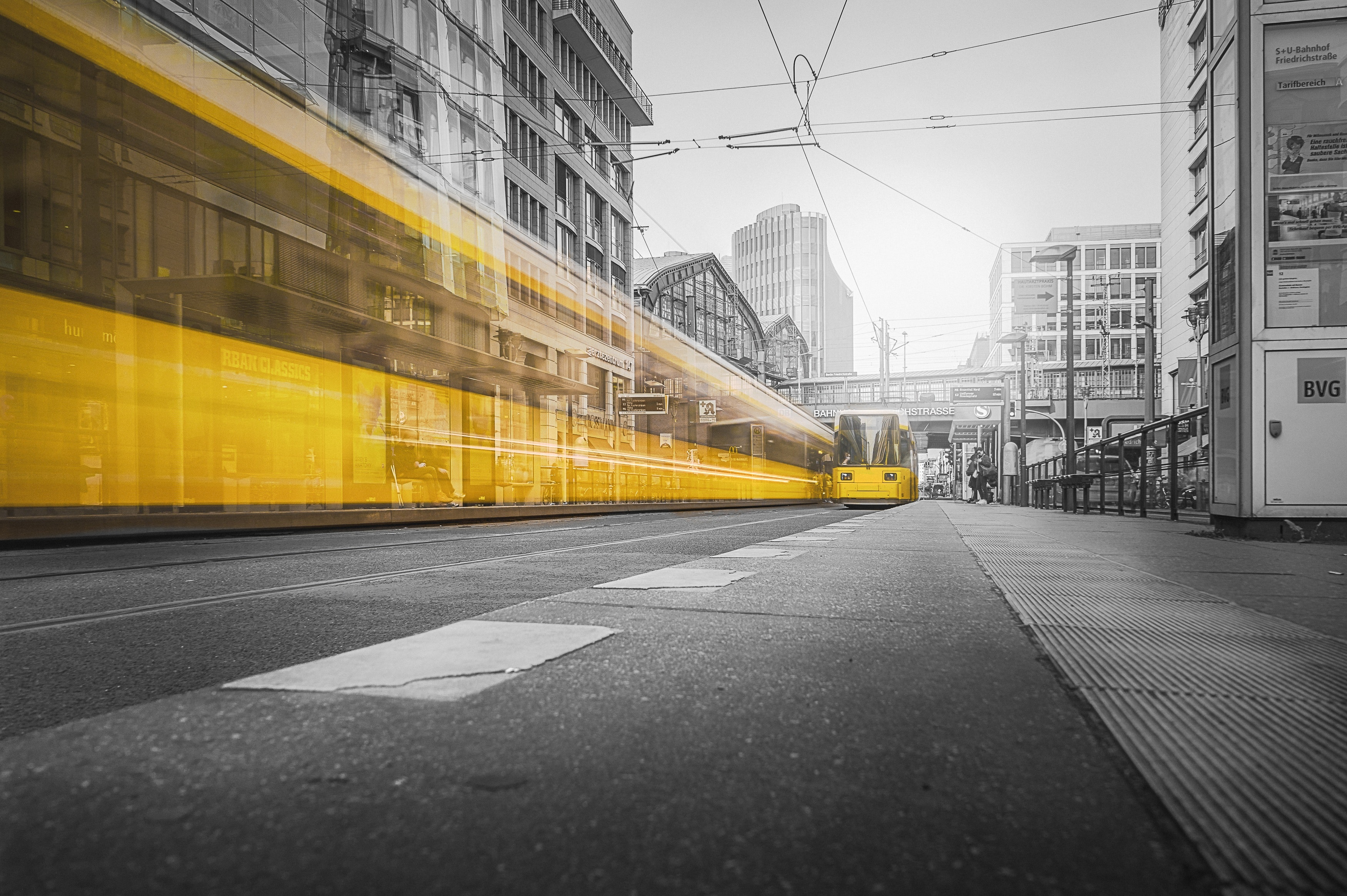 blurred image of yellow train over black and white city street